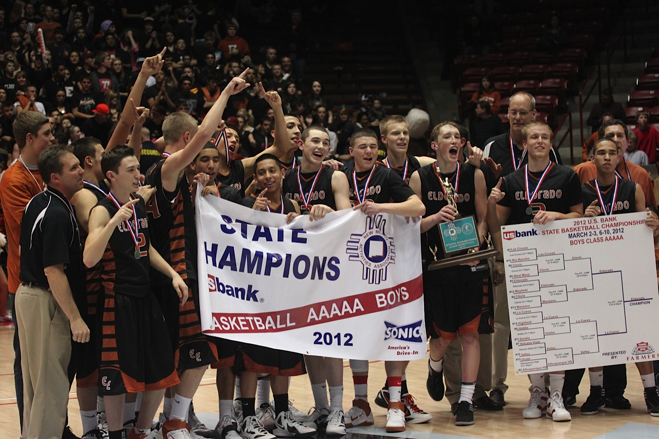 Basketball team with state champions poster celebrating